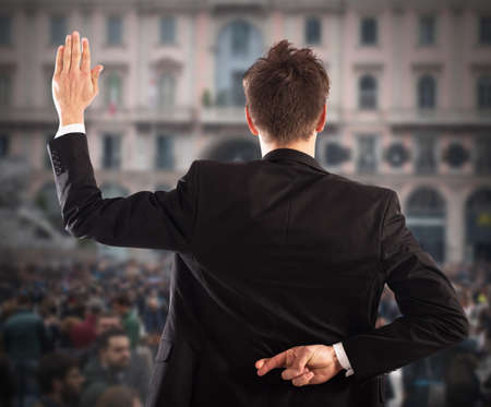 falsehood: Man makes gesture with hand behind back Stock Photo