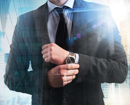corporate building: Elegant businessman with clock on skyscrapers background