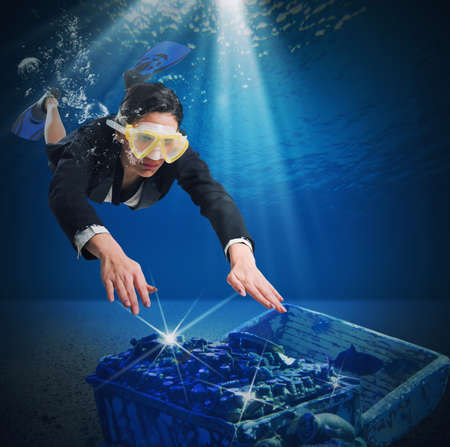 finds: Business woman swimming underwater finds a treasure