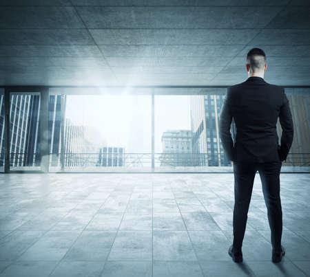 liderazgo empresarial: El hombre de negocios en una oficina con vistas a la ciudad Foto de archivo