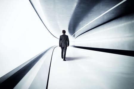 tunnel portals: Businessman walks in a futuristic steel tunnel