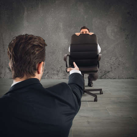 accused: Employee hiding behind chair fearful of boss
