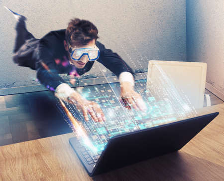 Man with mask looks at a laptop