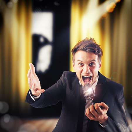 showman: Man screaming at the microphone on theatre Stock Photo