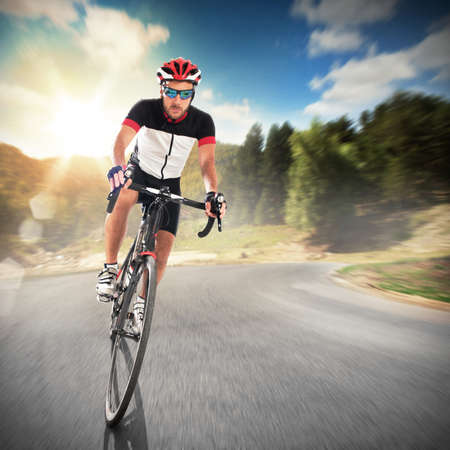 road cycling: Cyclist cycling road in a natural landscape Stock Photo