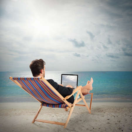 tourists stop: Man on deckchair with laptop at beach