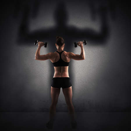 woman shadow: Muscular woman looks at her big shadow Stock Photo