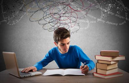 literature: estudio de muchacho adolescente con la computadora y libros Foto de archivo