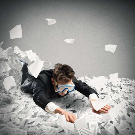 frustrate: Businessman with mask swims between the sheets Stock Photo