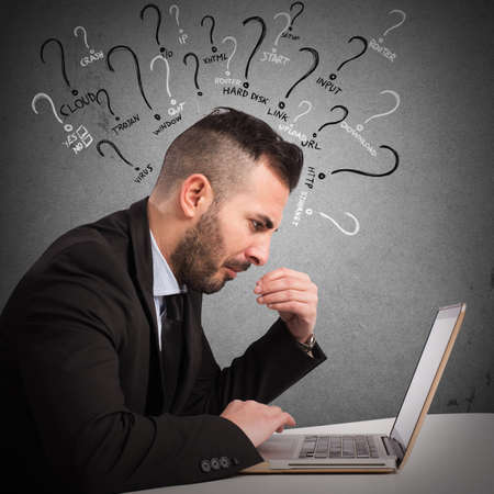 Businessman with quizzical expression at the computer