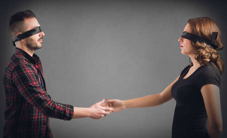 Strangers man and woman blindfolded shake hands Imagens