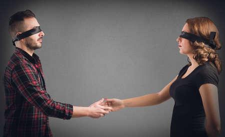 Strangers man en vrouw geblinddoekt schudden elkaar de hand Stockfoto