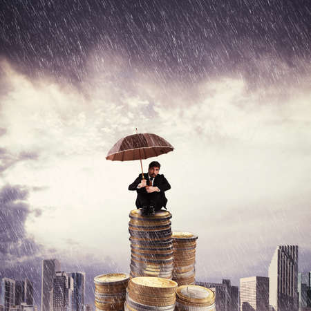 Businessman on top of a coins stack