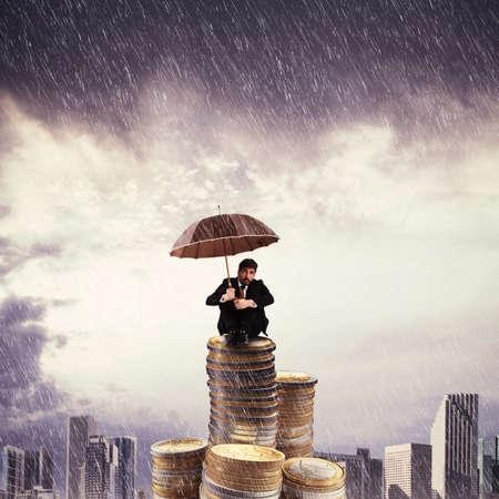 uomo sotto la pioggia: Imprenditore in cima ad una pila di monete