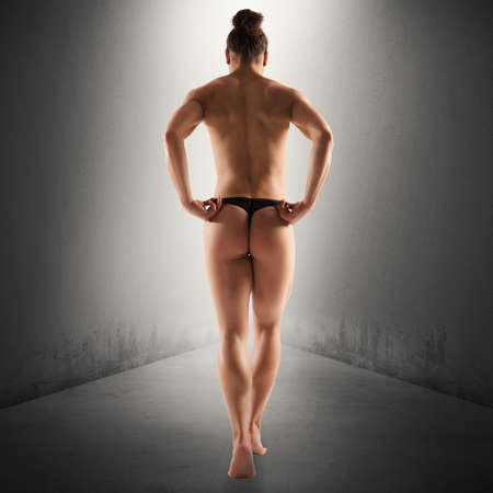 Muscular woman with thong walking from behind Stock Photo