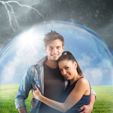 risky love: Smiling couple sheltered by a transparent ball