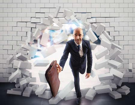 pared rota: El hombre de negocios con el bolso rompe a través de una pared