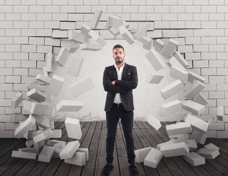 Hombre con una pared de ladrillo roto a través