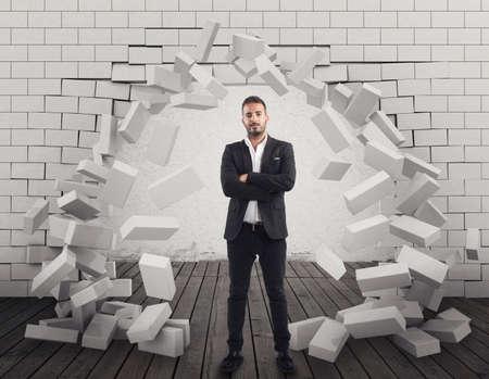 Man with a brick wall broken through