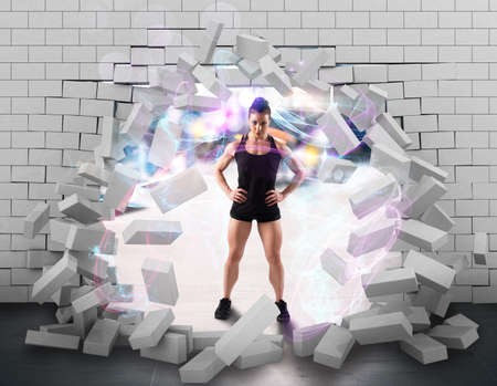 Muscular woman behind a broken brick wall