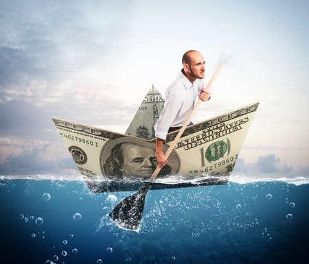 Businessman paddling on a big banknote boat