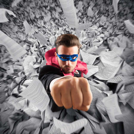 Empresario de superhéroes escape de una pila de hojas Foto de archivo