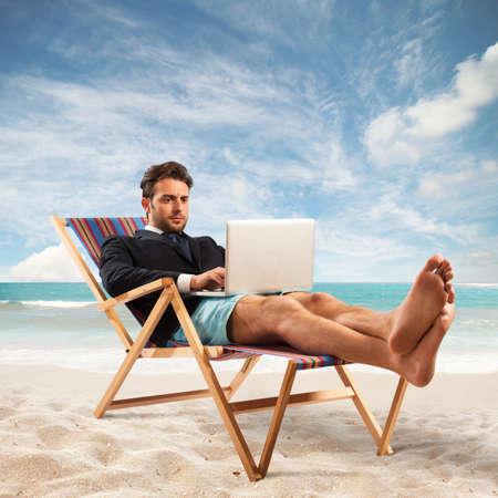 ビーチでコンピューターで実業家を動作します。