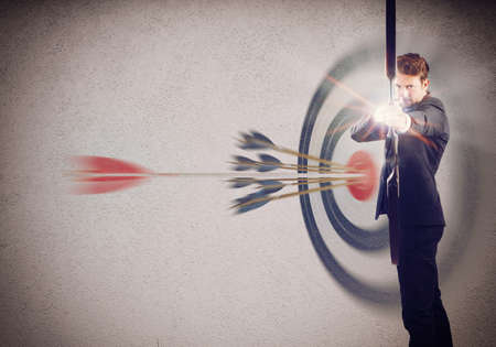 beat the competition: Businessman with bow and background with target Stock Photo