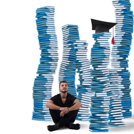 between: Boy sitting between stacks of study books Stock Photo