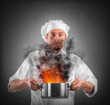 Chef shocked holding a pot with flames