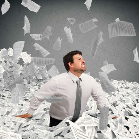 overwork: Businessman goes out from a sheets pile