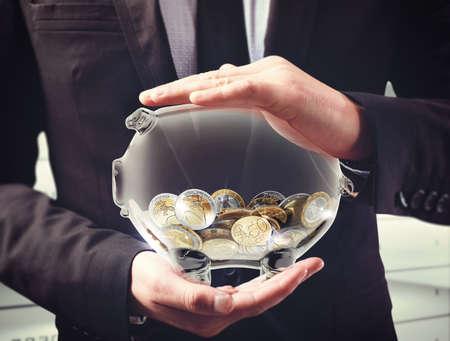 남자는 동전 투명 돼지 저금통을 보유하고