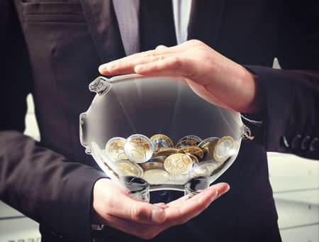El hombre sostiene una hucha transparente con las monedas Foto de archivo