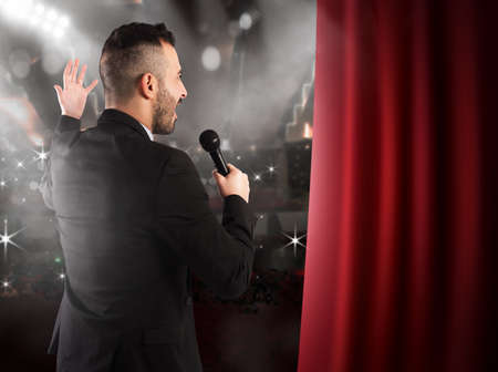 stage performer: Man talking on microphone on theater stage Stock Photo