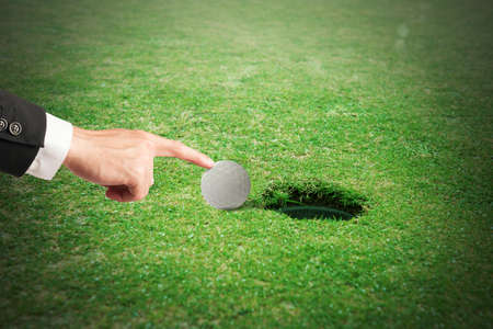 trickster: Hand pushes the ball in the hole Stock Photo