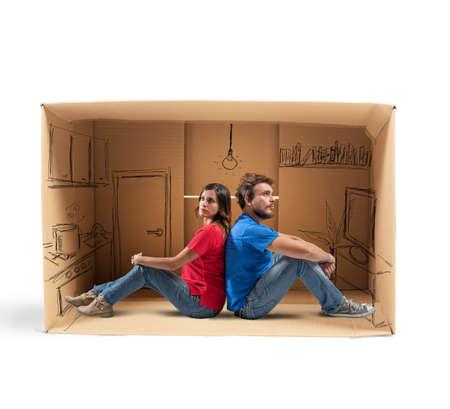 Paar in een huis ontworpen in kartonnen Stockfoto