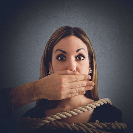 woman tied: Man covering mouth to a woman tied Stock Photo
