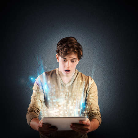 Boy amazed by bright light on tablet Stock Photo