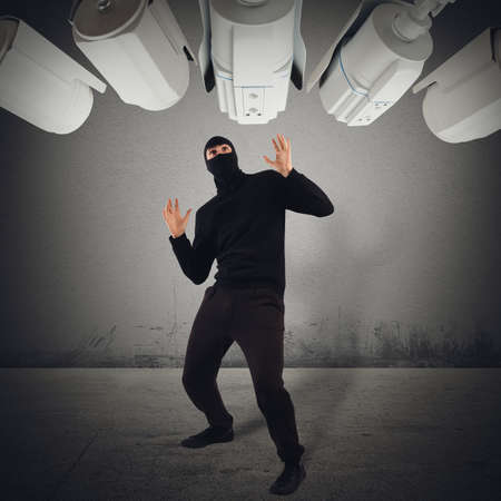 Cameras pointed at a hooded fearful man Stock Photo