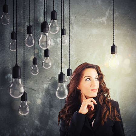 unlit: Woman with lit lightbulb among unlit bulbs