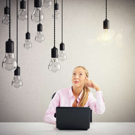 elaboration: Woman with laptop and lit light bulb Stock Photo