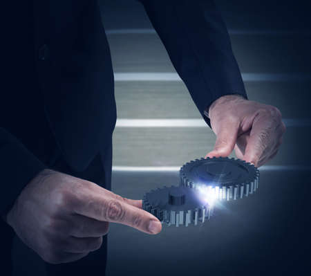 Businessman engages two pieces of mechanism gears Stock Photo
