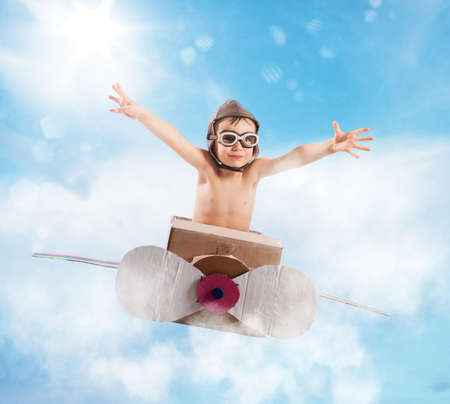 fly: Child with cardboard airplane in the sky Stock Photo