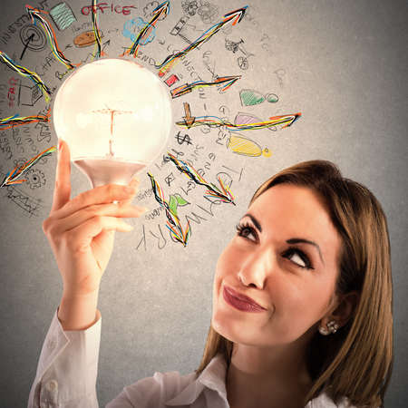 thinks: Businesswoman looks at a lit light bulb Stock Photo