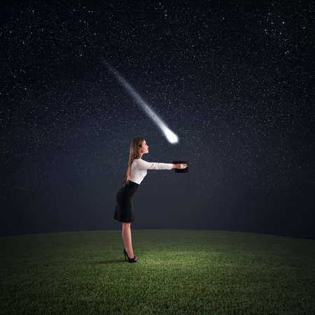 attain: Woman takes a falling star with hat Stock Photo