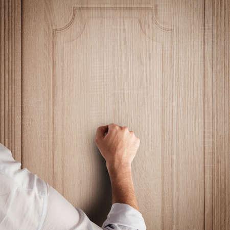 knock on door: Business man knocks to a wooden door Stock Photo