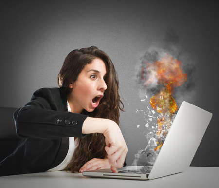 overheating: Astonished woman looks at the computer inflamed