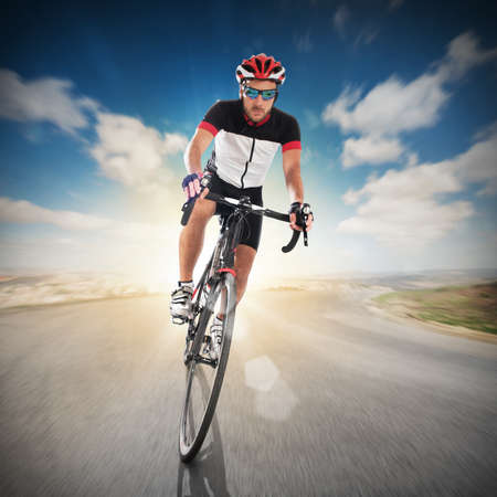 faster: Cyclist with helmet pedaling faster on road