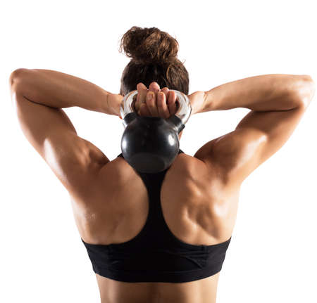 potency: Muscular woman from behind trains with kettlebell