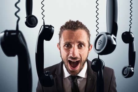 agitated: Angry businessman screams between black handsets phones